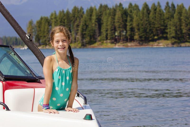 Κορίτσι που οδηγά motorboat σε μια όμορφη λίμνη στοκ εικόνες