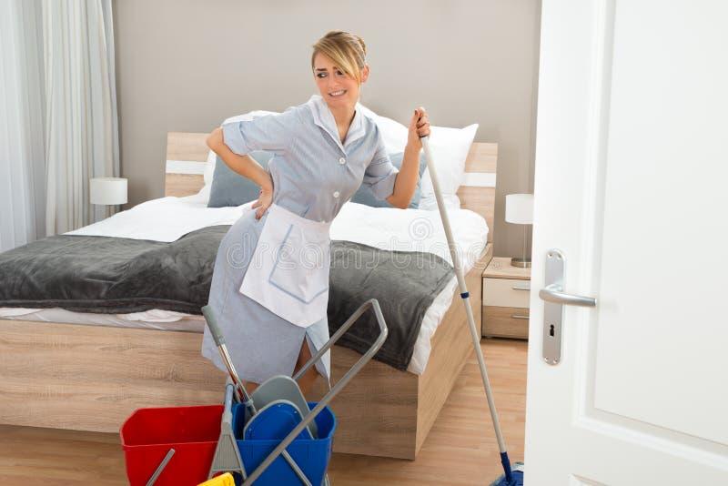 Κορίτσι που πάσχει από τον πόνο στην πλάτη καθαρίζοντας το δωμάτιο ξενοδοχείου στοκ εικόνες