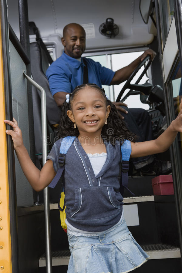 Κορίτσι που παίρνει από το σχολικό λεωφορείο στοκ εικόνα