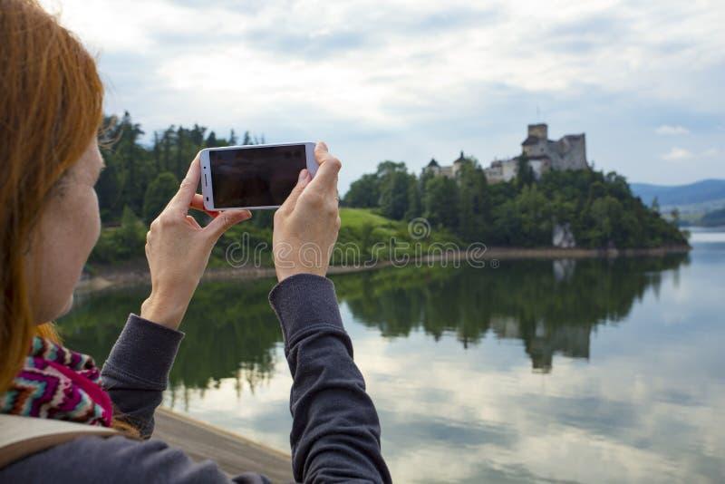 Κορίτσι που παίρνει μια εικόνα ενός όμορφου κάστρου σε μια ακτή λιμνών στοκ εικόνες με δικαίωμα ελεύθερης χρήσης