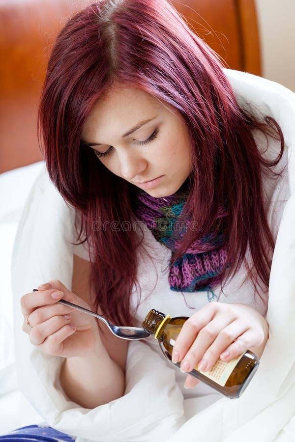 Κορίτσι που παίρνει το σιρόπι βήχα στοκ φωτογραφία