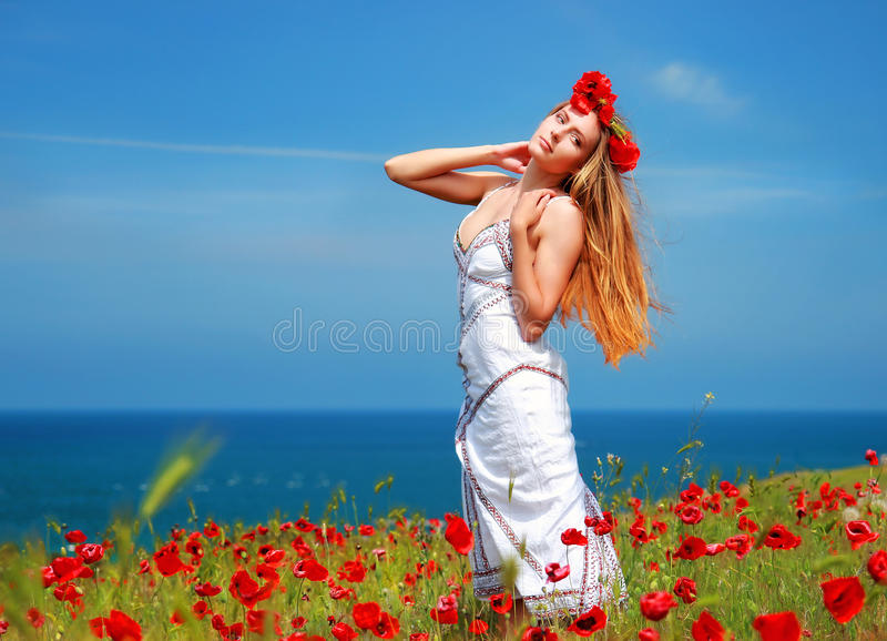 Κορίτσι που περπατά στον τομέα παπαρουνών στοκ φωτογραφία