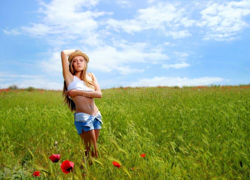 Κορίτσι που περπατά στον τομέα παπαρουνών στοκ εικόνες