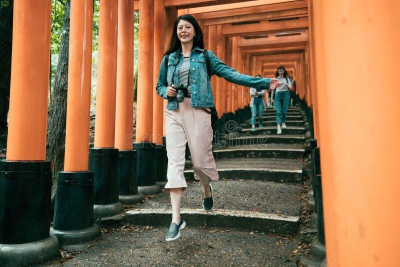 Κορίτσι που πηδά χαρωπά κάτω από το σκαλοπάτι κάτω από την κόκκινη πύλη στοκ φωτογραφία με δικαίωμα ελεύθερης χρήσης