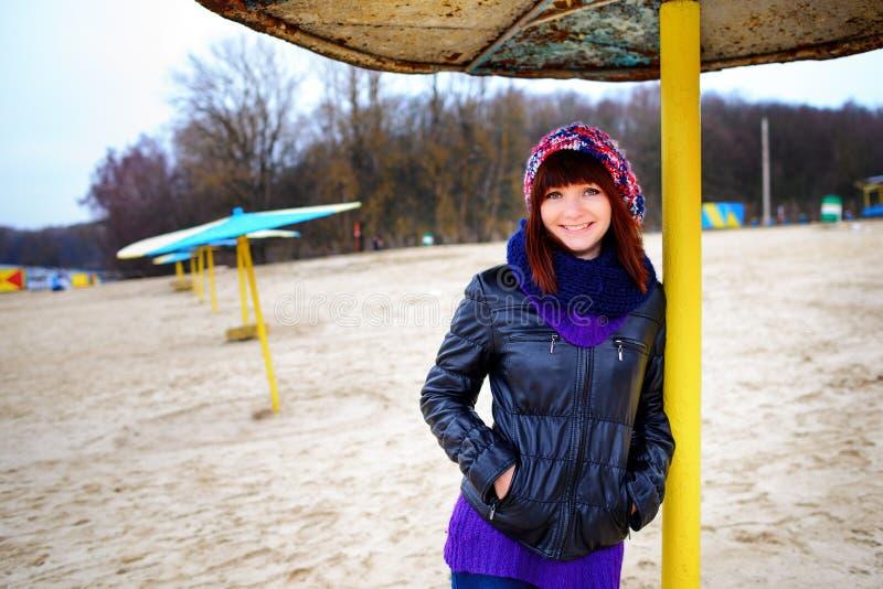 Κορίτσι που στέκεται κάτω από μια ομπρέλα στην παραλία το φθινόπωρο στοκ εικόνες