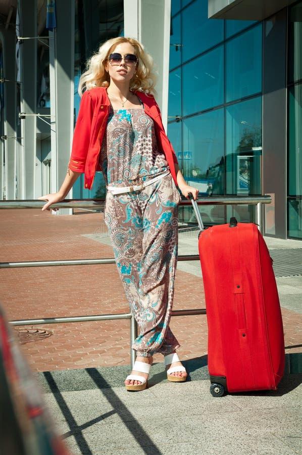 Κορίτσι που στέκεται με μια βαλίτσα κοντά στο σταθμό στοκ εικόνα με δικαίωμα ελεύθερης χρήσης