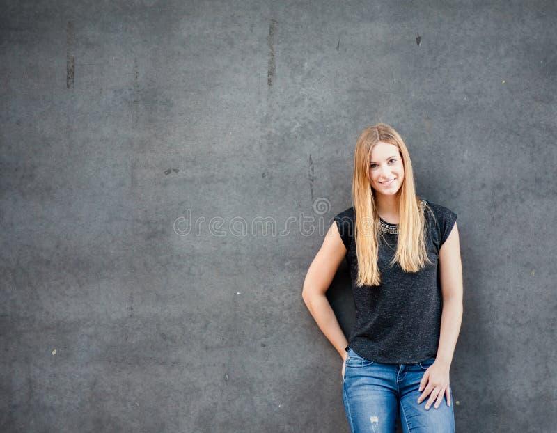 Κορίτσι που στέκεται μπροστά από το συμπαγή τοίχο στοκ φωτογραφίες