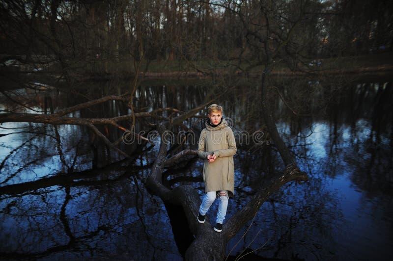 Κορίτσι που στέκεται σε ένα πεσμένο δέντρο κοντά στη λίμνη την πρώιμη άνοιξη στοκ εικόνες με δικαίωμα ελεύθερης χρήσης