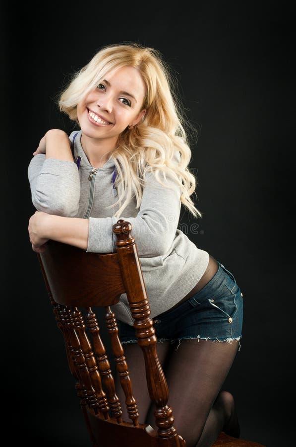 Κορίτσι που στέκεται σε μια καρέκλα στοκ φωτογραφίες