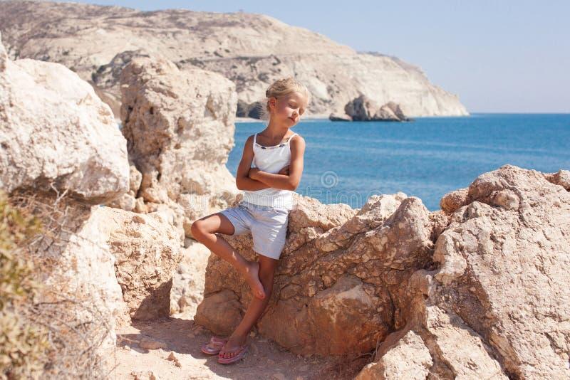 Κορίτσι που στέκεται στον απότομο βράχο στην ακτή στοκ φωτογραφίες