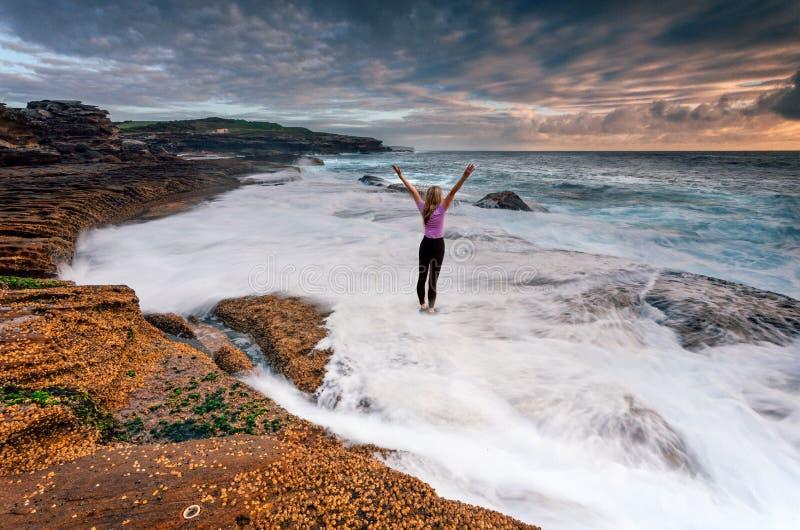 Κορίτσι που στέκεται στους βράχους ως ωκεάνιο πλύσιμο κυμάτων μετά από τα πόδια της στοκ φωτογραφίες