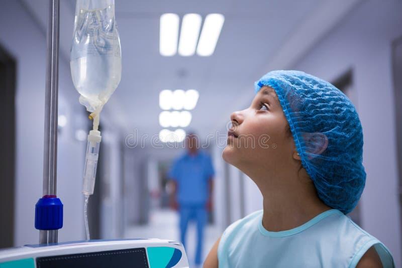 Κορίτσι που στέκεται στο διάδρομο και που εξετάζει IV σταλαγματιά στοκ εικόνα με δικαίωμα ελεύθερης χρήσης