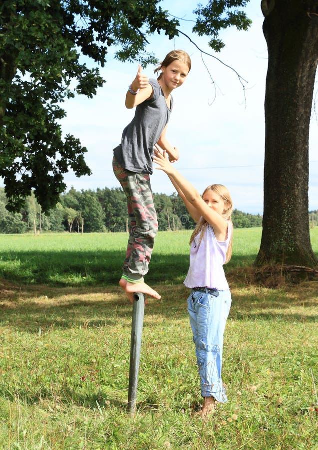 Κορίτσι που στέκεται στο στυλοβάτη σιδήρου με τον αντίχειρα επάνω στοκ εικόνες με δικαίωμα ελεύθερης χρήσης
