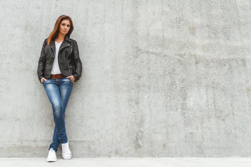 Κορίτσι που στέκεται στο συμπαγή τοίχο στοκ φωτογραφία