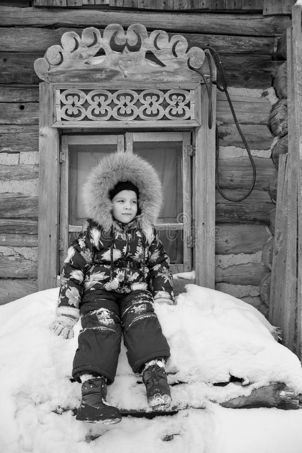 Κορίτσι που στέκεται το χειμώνα κοντά στο παλαιό ξύλινο σπίτι και το χαρασμένο παράθυρο στοκ εικόνες