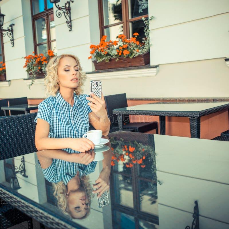 Κορίτσι που στηρίζεται σε έναν καφέ στοκ εικόνα