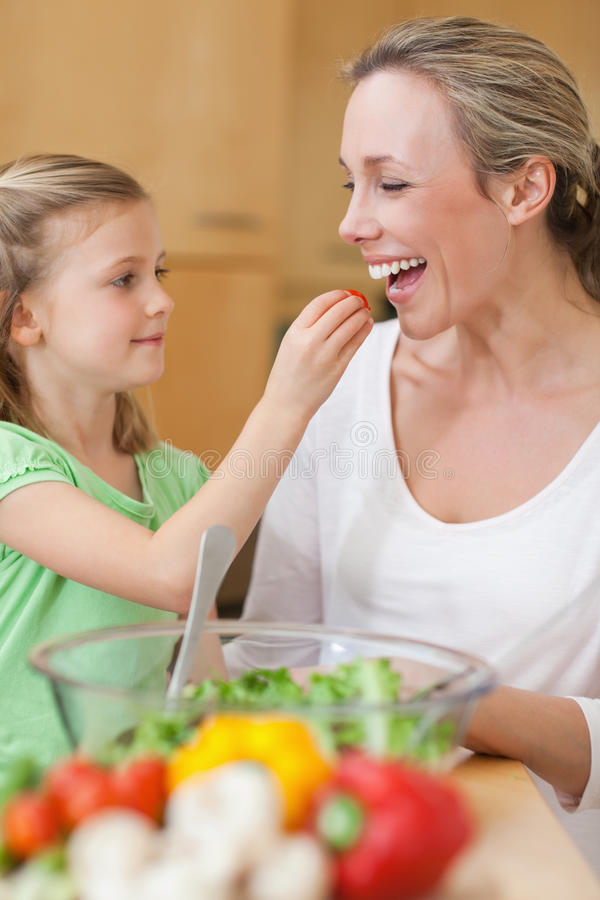 Κορίτσι που ταΐζει τη μητέρα της με τη σαλάτα στοκ φωτογραφία