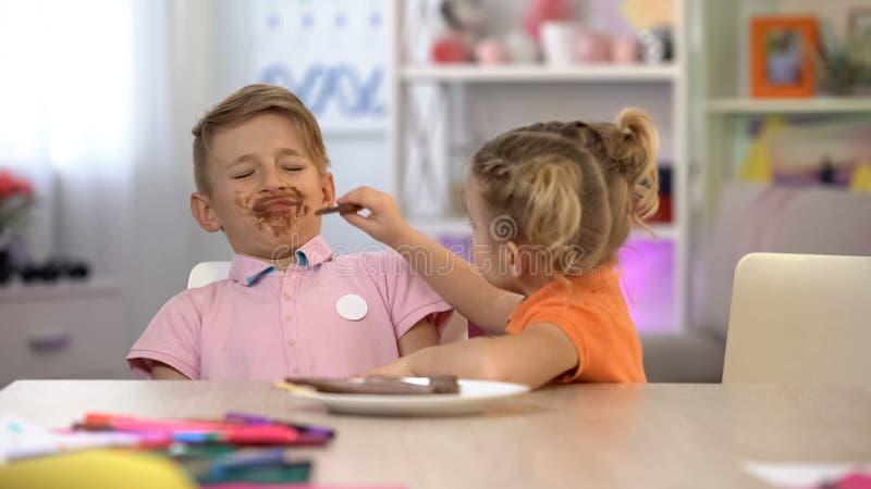 Κορίτσι που ταΐζει το λερωμένο αγόρι με τη σοκολάτα, γλυκά που παρατρώει, προβλήματα στομαχιών στοκ εικόνες με δικαίωμα ελεύθερης χρήσης