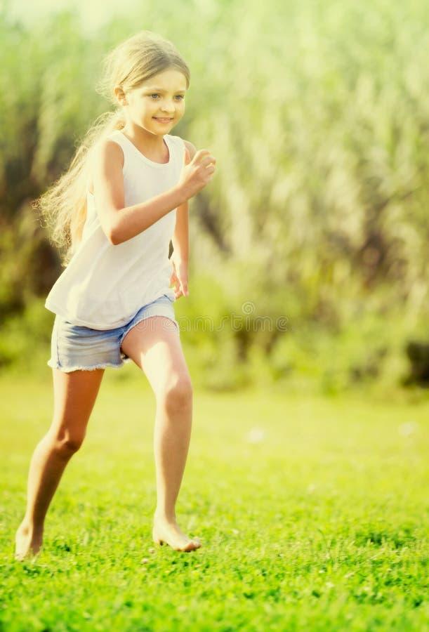 Κορίτσι που τρέχει και που πηδά στη χλόη στοκ εικόνα