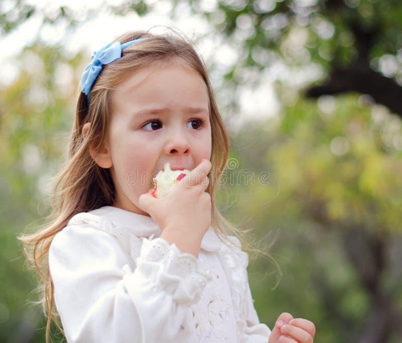 Κορίτσι που τρώει ένα μήλο στοκ εικόνα