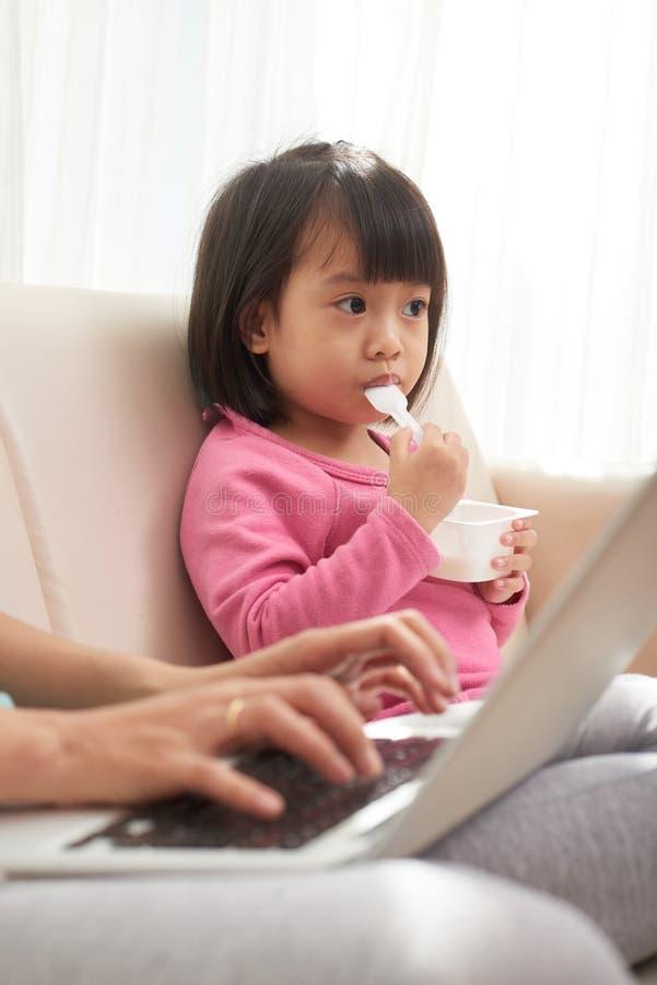Κορίτσι που τρώει στον καναπέ με την εργαζόμενη μητέρα στοκ φωτογραφία με δικαίωμα ελεύθερης χρήσης