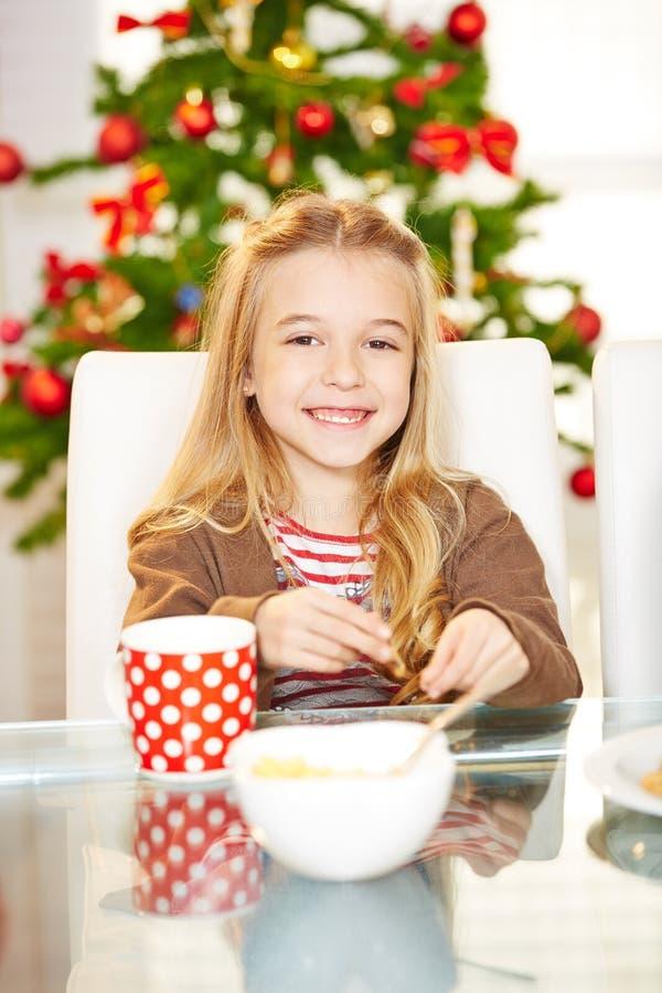 Κορίτσι που τρώει τα μπισκότα στα Χριστούγεννα στοκ εικόνες