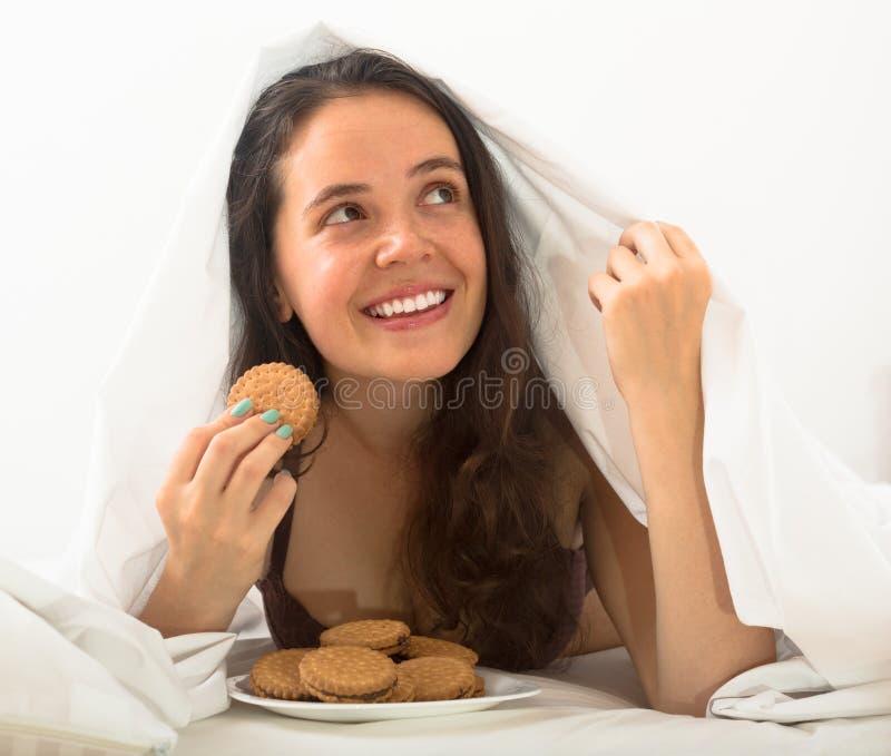 Κορίτσι που τρώει τα μπισκότα στο κρεβάτι στοκ εικόνες