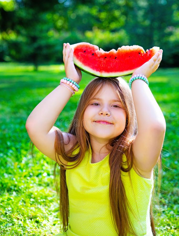 Κορίτσι που τρώει το καρπούζι υπαίθριο στοκ εικόνα