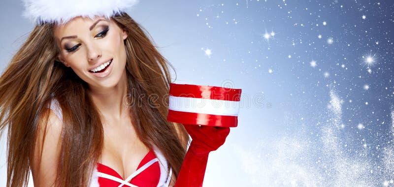 Κορίτσι που φορά τα ενδύματα Άγιου Βασίλη με τα Χριστούγεννα στοκ εικόνες