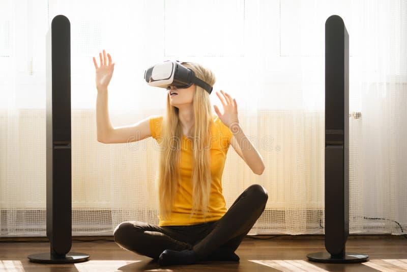 Κορίτσι που φορά τα προστατευτικά δίοπτρα εικονικής πραγματικότητας στο σπίτι στοκ εικόνες