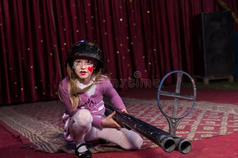 Κορίτσι που φορά το κράνος που σκύβει στη σκηνή με το πυροβόλο όπλο στοκ φωτογραφία με δικαίωμα ελεύθερης χρήσης