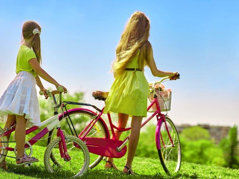Κορίτσι που φορά το κόκκινο ποδήλατο γύρων φορεμάτων σημείων Πόλκα στο πάρκο στοκ εικόνα