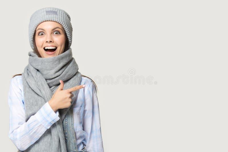 Κορίτσι που φορά το πλεκτό θερμό μαντίλι καπέλων που δείχνει το δάχτυλο στο copyspace στοκ φωτογραφίες