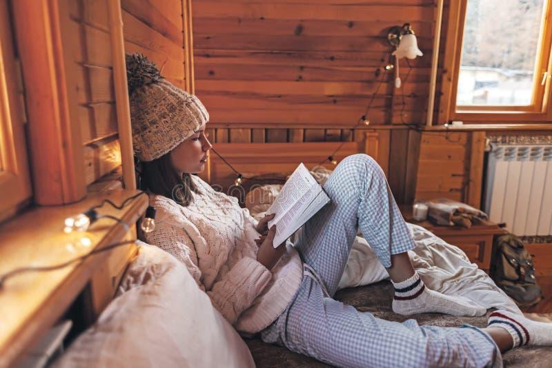 Κορίτσι που χαλαρώνει και διαβάζει βιβλίο σε ζεστή καμπίνα κορμών το χειμώνα στοκ φωτογραφίες με δικαίωμα ελεύθερης χρήσης