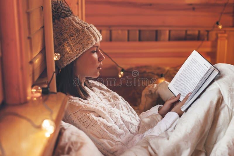 Κορίτσι που χαλαρώνει και διαβάζει βιβλίο σε ζεστή καμπίνα κορμών το χειμώνα στοκ εικόνες