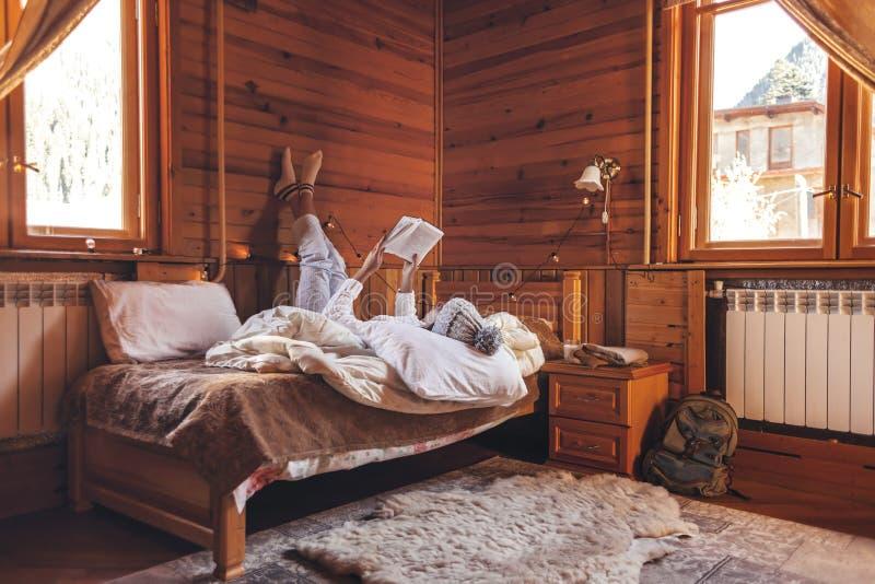 Κορίτσι που χαλαρώνει και διαβάζει βιβλίο σε ζεστή καμπίνα κορμών το χειμώνα στοκ φωτογραφία με δικαίωμα ελεύθερης χρήσης