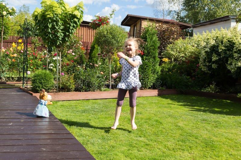 Κορίτσι που χορεύει στον όμορφο ανθίζοντας κήπο στοκ εικόνες