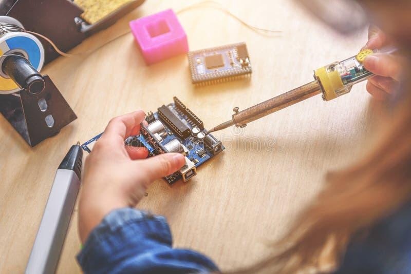 Κορίτσι που χρησιμοποιεί με βεβαιότητα το συγκολλώντας σίδηρο στοκ εικόνες
