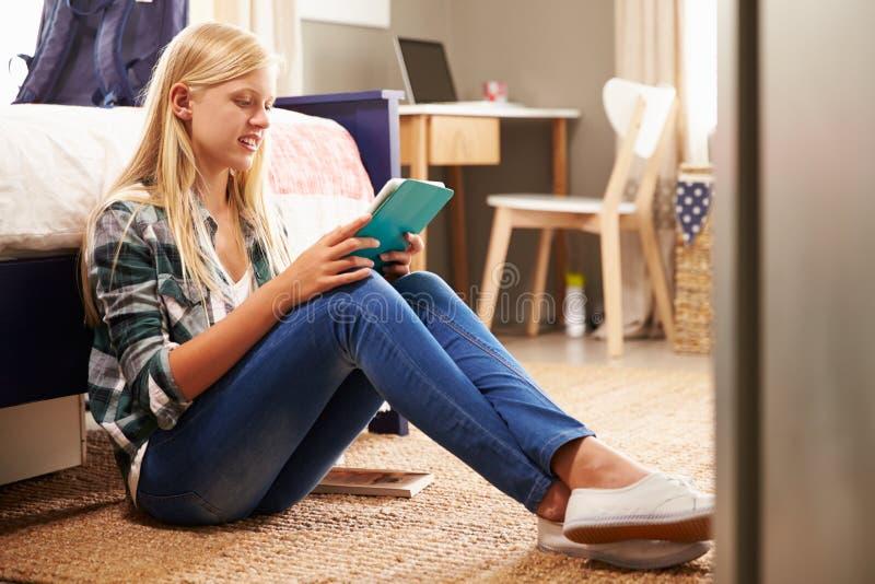 Κορίτσι που χρησιμοποιεί την ψηφιακή ταμπλέτα στην κρεβατοκάμαρά της στοκ εικόνες