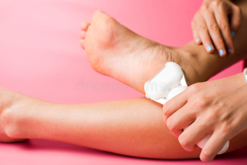Κορίτσι που χρησιμοποιεί το αρχείο ποδιών για να καθαρίσει το σκληρό δέρμα στοκ φωτογραφία
