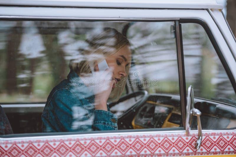 Κορίτσι που χρησιμοποιεί το smartphone σε minivan στοκ εικόνα