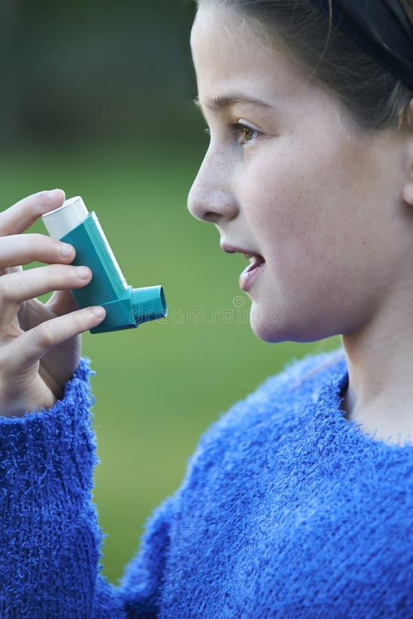 Κορίτσι που χρησιμοποιεί Inhaler για να μεταχειριστεί την επίθεση άσθματος στοκ εικόνα