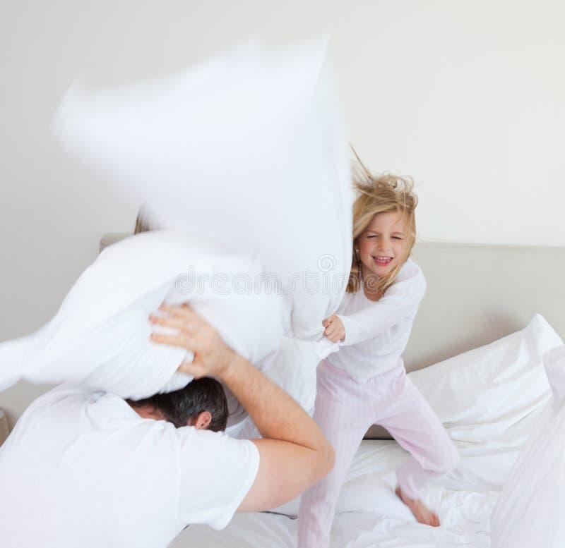Κορίτσι που χτυπά τον πατέρα της με το μαξιλάρι στοκ φωτογραφίες