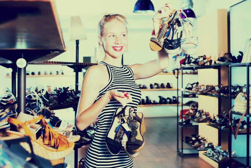 Κορίτσι που ψωνίζει πολλά ζευγάρια παπουτσιών στοκ εικόνες με δικαίωμα ελεύθερης χρήσης