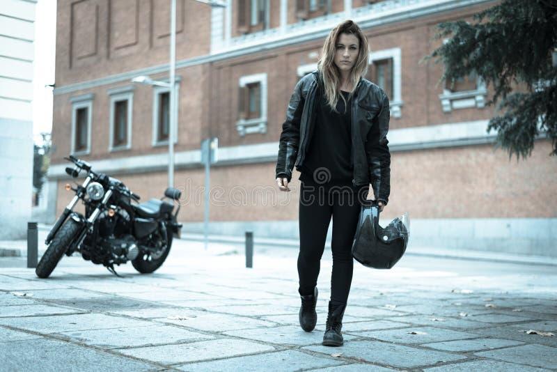 Κορίτσι ποδηλατών σε ένα σακάκι δέρματος σε μια μοτοσικλέτα στοκ φωτογραφία