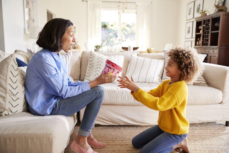 Κορίτσι προ-εφήβων που δίνει της τη μητέρα σπιτικό διακοσμημένο δοχείο εγκαταστάσεων, πλάγια όψη στοκ φωτογραφία με δικαίωμα ελεύθερης χρήσης