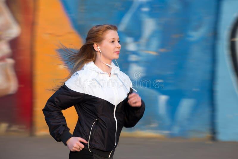 Κορίτσι δρομέων η πρακτική εκτός από τον τοίχο γκράφιτι στοκ εικόνα με δικαίωμα ελεύθερης χρήσης