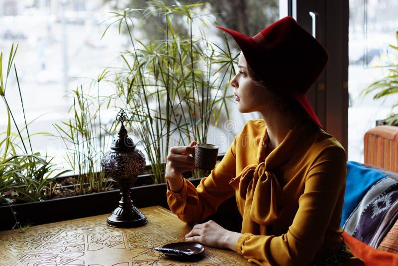 Κορίτσι σε έναν καφέ με ένα φλιτζάνι του καφέ και ένα καπέλο Πορτρέτο του αισθησιακού νέου κοριτσιού που φορά το πλαδαρές καπέλο  στοκ εικόνα με δικαίωμα ελεύθερης χρήσης