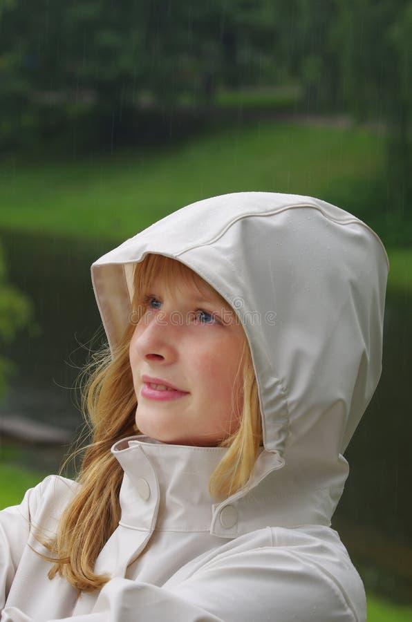 Κορίτσι σε ένα αδιάβροχο στη βροχή στοκ φωτογραφίες