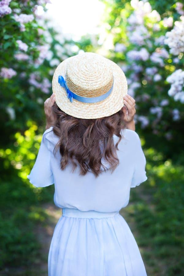 Κορίτσι σε ένα καπέλο αχύρου με μια μπλε κορδέλλα σε ένα απόγευμα άνοιξη E Καθιερώνουσα τη μόδα περιστασιακή εξάρτηση καλοκαιριού στοκ εικόνες
